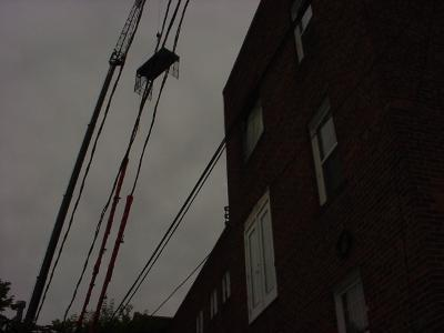 Image of a piece of steel balcony being craned into place.