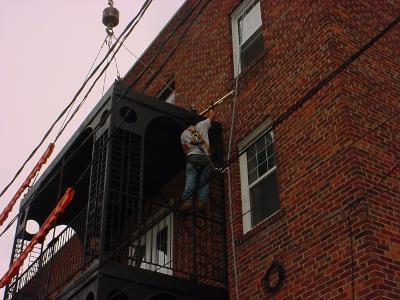Image securing third tier to brick building.