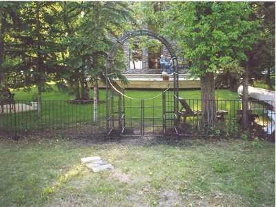 Image of a rounded arbour and accompanying iron fence.